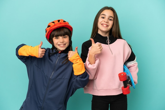 Маленькие сестры, практикующие езда на велосипеде и фигуристы, изолированные на синем фоне, показывая большие пальцы вверх обеими руками и улыбаясь