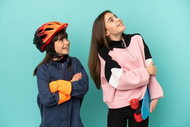Маленькие сестры, практикующие езда на велосипеде и фигуристы, изолированные на синем фоне, глядя вверх, улыбаясь