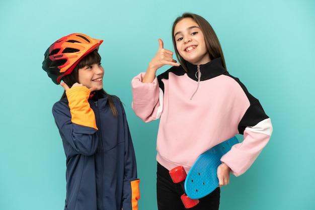 Маленькие сестры, практикующие езда на велосипеде и фигурист, изолированные на синем фоне, делая телефонный жест. перезвони мне знак