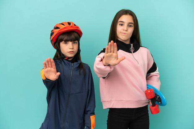 Маленькие сестры, занимающиеся велоспортом, и фигуристки изолированы на синем фоне, делая жест стоп, отрицая ситуацию, которая думает неправильно