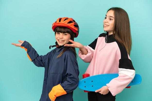 Маленькие сестры, практикующие езда на велосипеде и фигуристки, изолированные на синем фоне, указывая назад и представляя продукт