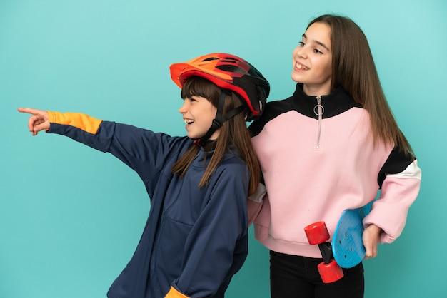 제품을 제시하기 위해 측면을 가리키는 파란색 배경에 고립 된 사이클링과 스케이팅을 연습하는 작은 자매