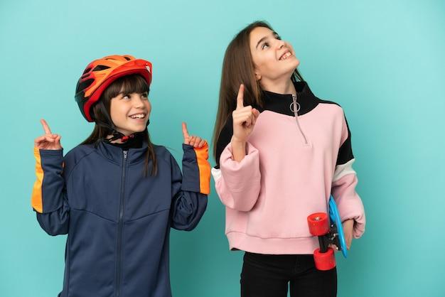 검지 손가락으로 가리키는 파란색 배경에 격리된 사이클링과 스케이팅을 연습하는 어린 자매들