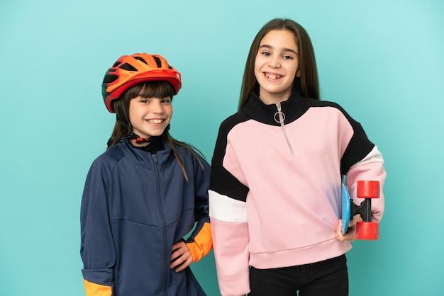 Маленькие сестры, практикующие езда на велосипеде и фигуристки, изолированные на синем фоне, позируют с руками на бедрах и улыбаются