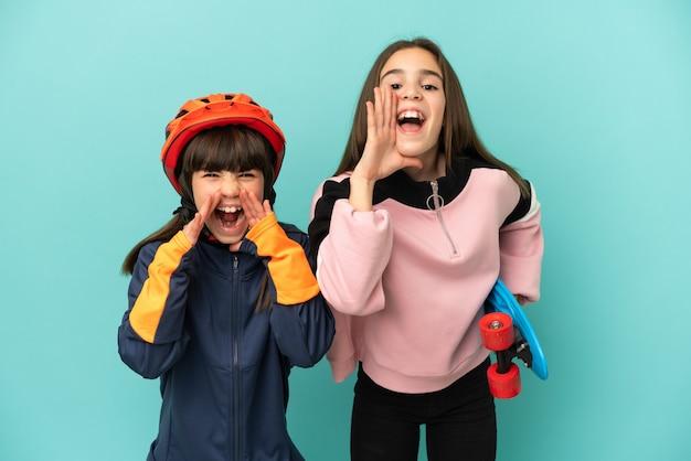 Маленькие сестры, практикующие езда на велосипеде и фигуристки, изолированные на синем фоне, кричат и что-то объявляют