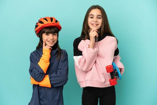 Маленькие сестры, практикующие велоспорт и фигуристки, изолированные на синем фоне, улыбаясь со сладким выражением лица