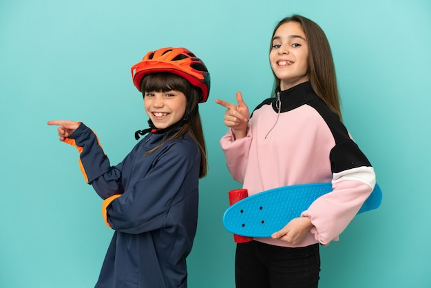 Little sisters practicing cycling and skater isolated on blue background pointing finger to the side in lateral position
