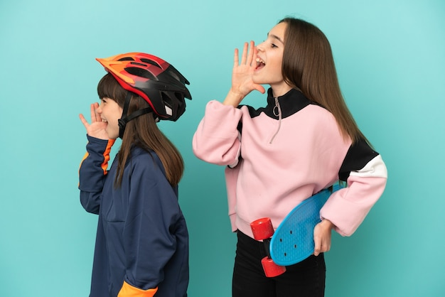 Little sisters practicing cycling and skater isolated on blue background shouting with mouth wide open to the lateral