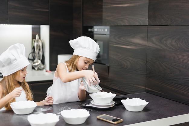Маленькие сестры готовят тесто для приготовления печенья на кухне