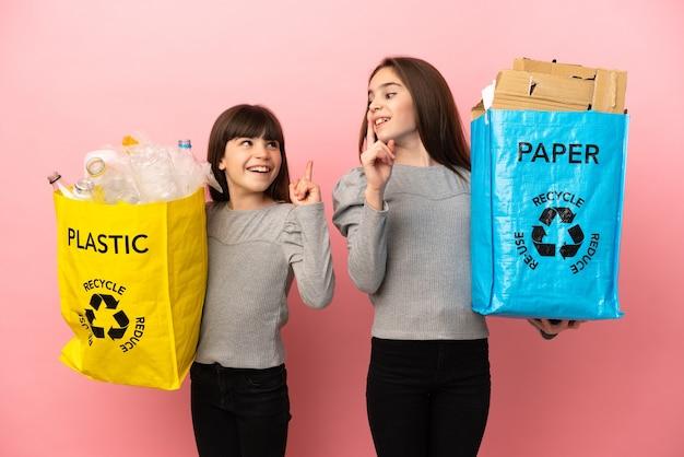 종이와 플라스틱을 재활용하는 여동생은 손가락을 들어 올리면서 해결책을 실현하려고합니다.