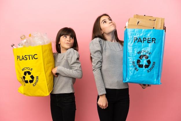 종이와 플라스틱을 재활용하는 여동생은 어깨를 들어 올리는 동안 의심 제스처를 만듭니다.