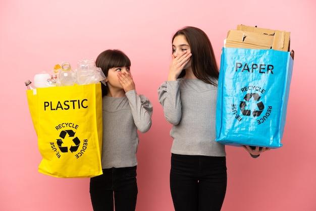 不適切なことを言うために手で口を覆っているピンクの背景に分離された紙とプラスチックをリサイクルする妹
