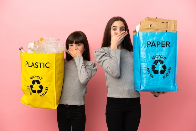 분홍색 배경에 격리된 종이와 플라스틱을 재활용하는 작은 자매들은 부적절한 말을 하기 위해 손으로 입을 가리고 있습니다