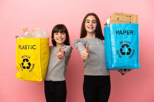 분홍색 배경에 격리된 종이와 플라스틱을 재활용하는 작은 자매들은 좋은 일이 일어났기 때문에 엄지손가락을 치켜드는 제스처를 합니다