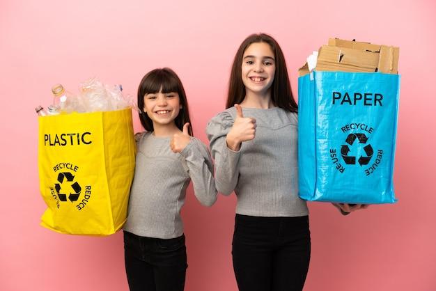 ピンクの背景に分離された紙とプラスチックをリサイクルする妹は、両手と笑顔で親指を立てるジェスチャーを与える