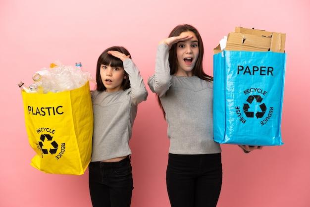 ピンクの背景に分離された紙とプラスチックをリサイクルする妹はちょうど何かを実現し、解決策を意図しています