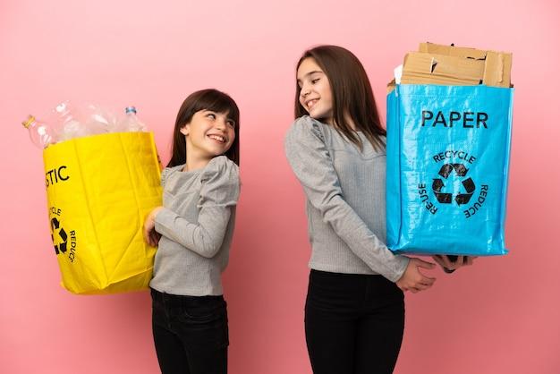 笑顔で肩越しに見ているピンクの背景に分離された紙とプラスチックをリサイクルする妹