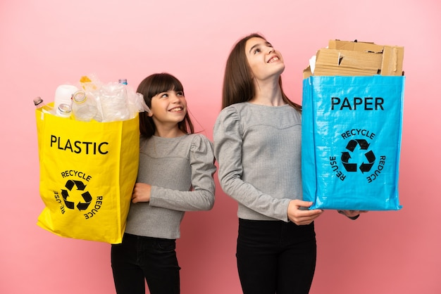 笑顔で見上げるピンクの背景に分離された紙とプラスチックをリサイクルする妹