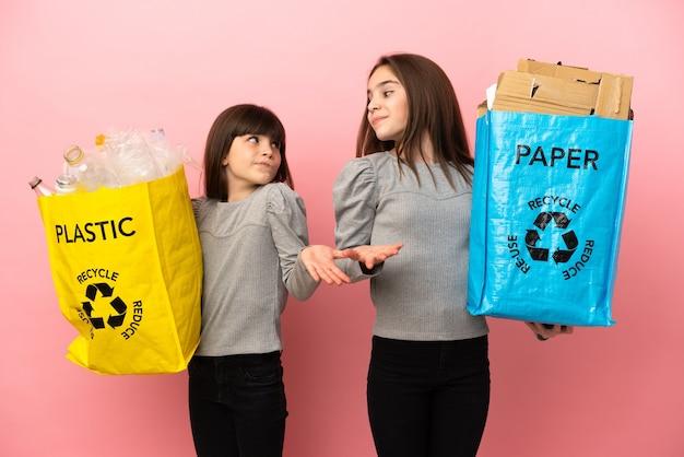 ピンクの背景に分離された紙とプラスチックをリサイクルする妹は、肩を持ち上げながら重要でないジェスチャーをします