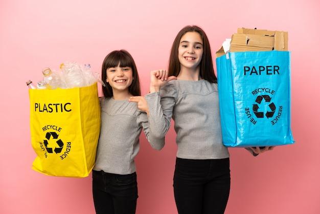 Маленькие сестры, перерабатывающие бумагу и пластик, изолированные на розовом фоне, гордые и самодовольные в любви к себе