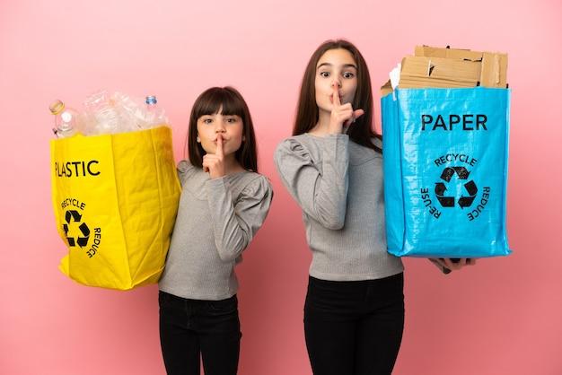 ピンクの背景に分離された紙とプラスチックをリサイクルする妹は、口に指を入れて沈黙のジェスチャーの兆候を示しています