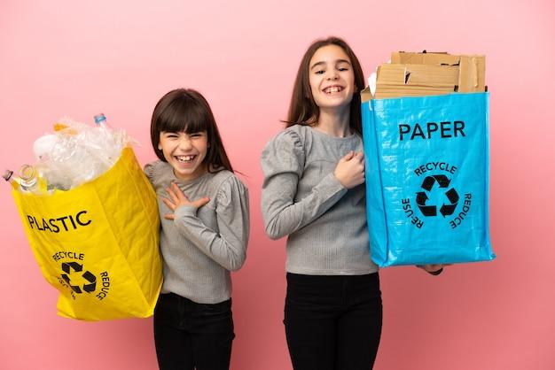 분홍색 배경에 격리된 종이와 플라스틱을 재활용하는 작은 자매들은 가슴에 손을 대면서 많이 웃고 있습니다