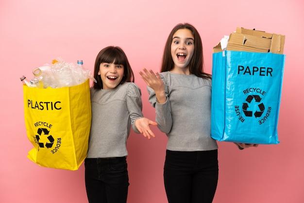 분홍색 배경에 격리된 종이와 플라스틱을 재활용하는 작은 자매들