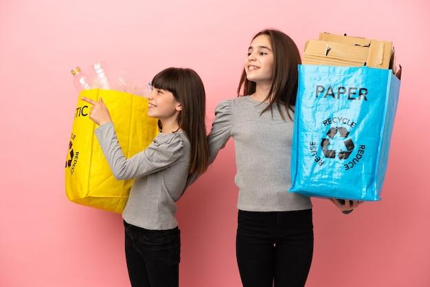 종이와 플라스틱을 재활용하는 작은 자매는 향해 웃고있는 동안 아이디어를 제시하는 격리