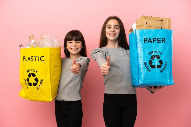 Little sisters recycling paper and plastic isolated on pink background giving a thumbs up gesture because something good has happened