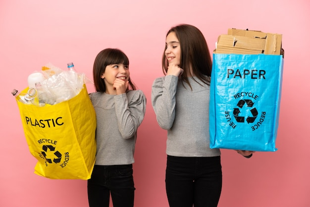 Little sisters recycling paper and plastic isolated on pink background looking looking at each other