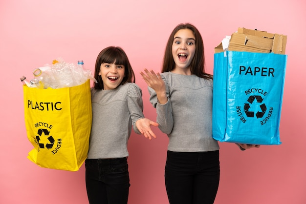 Little sisters recycling paper and plastic isolated on pink background with surprise and shocked facial expression