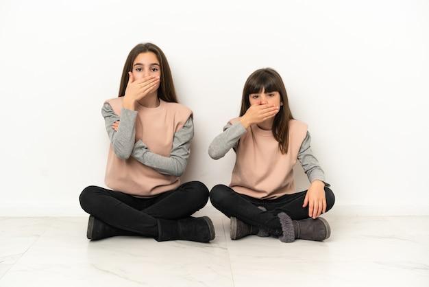 Маленькие сестры сидят на полу на белом фоне, прикрывая рот руками за то, что говорят что-то неуместное