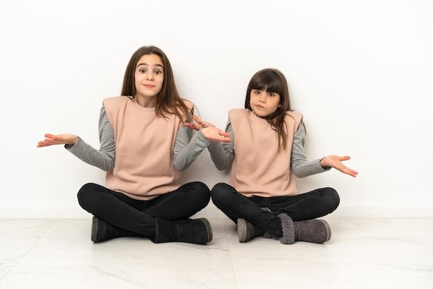 Маленькие сестры сидят на полу, изолированные на белом фоне, сомневаясь, поднимая руки и плечи