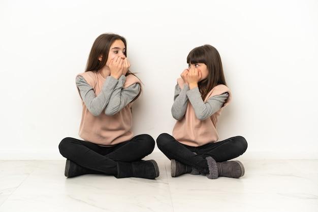 흰색 배경에 격리된 바닥에 앉아 있는 어린 자매들은 약간 긴장하고 손을 입에 대고 있는 것을 두려워합니다