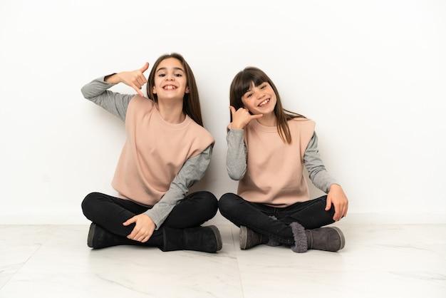 Маленькие сестры, сидя на полу, изолированные на белом фоне, делая телефонный жест. перезвони мне знак