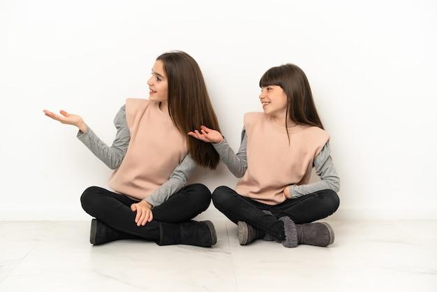 Маленькие сестры сидят на полу, изолированные на белом фоне, указывая назад и представляя продукт