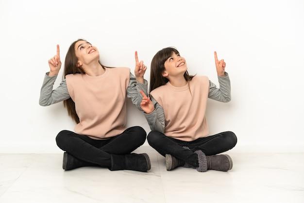 人差し指で指している白い背景で隔離の床に座っている妹は素晴らしいアイデア