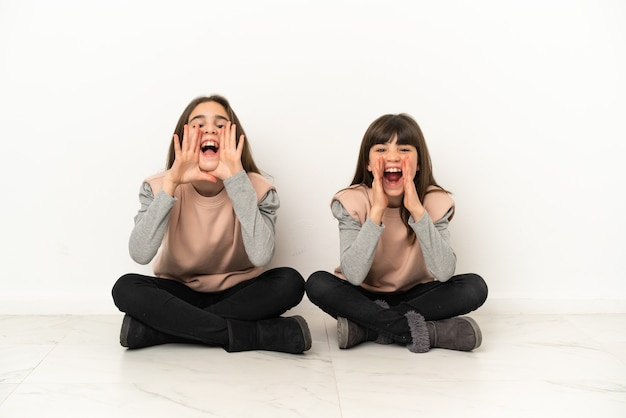 Маленькие сестры сидят на полу, изолированные на белом фоне, кричат и что-то объявляют