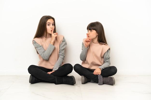 Маленькие сестры сидят на полу, изолированные на белом фоне, показывая знак закрывающегося рта и жест молчания