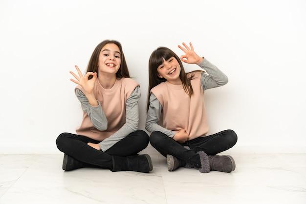 白い背景で隔離の床に座っている妹は指でokサインを示しています