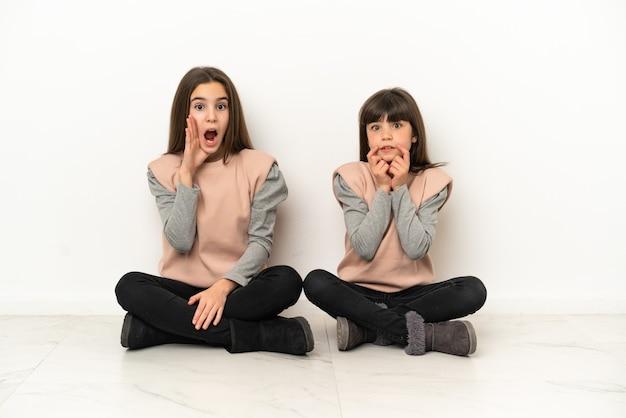 白い背景で隔離された床に座っている妹は、右を見ながら驚いてショックを受けました