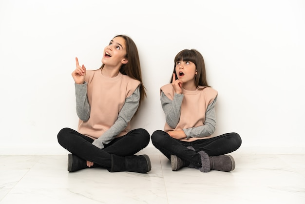 손가락을 가리키는 아이디어를 생각하는 흰색 배경에 고립 된 바닥에 앉아 작은 자매