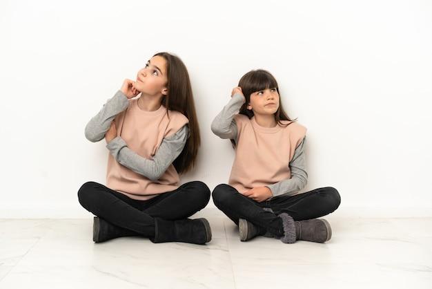 Маленькие сестры сидят на полу, изолированные на белом фоне, думая об идее, почесывая голову