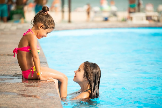 Little sisters swim in the pool