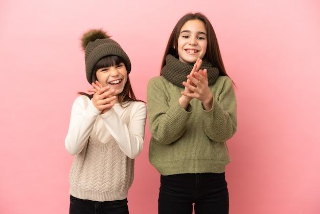 Маленькие сестры в зимней одежде на розовом фоне аплодируют после презентации на конференции