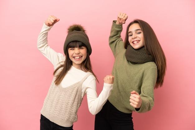 Маленькие сестры в зимней одежде на розовом фоне празднуют победу