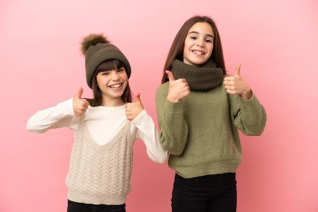 Маленькие сестры в зимней одежде на розовом фоне, показывая большие пальцы вверх обеими руками и улыбаясь