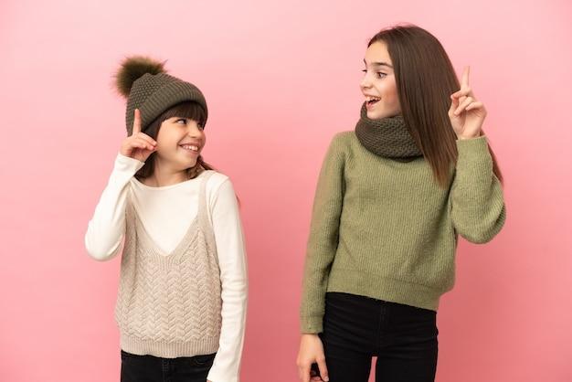 Маленькие сестры в зимней одежде на розовом фоне, намереваясь реализовать решение, подняв палец вверх