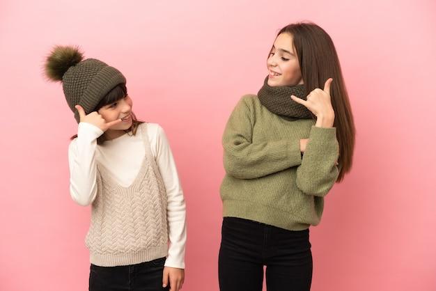 Маленькие сестры в зимней одежде, изолированные на розовом фоне, делая телефонный жест. перезвони мне знак