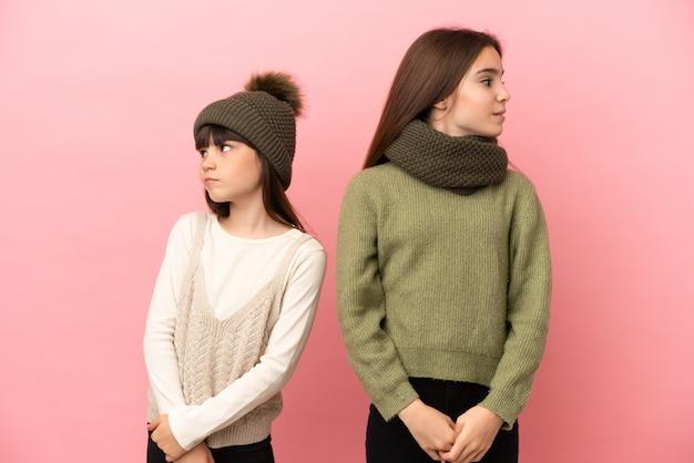 Маленькие сестры в зимней одежде на розовом фоне нервничают и напуганы